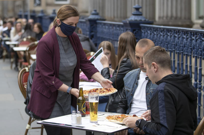 Meals are served at socially distanced tables on the street at Di Maggio's outdoor restaurant area in the city centre of Glasgow, Scotland, Monday July 6, 2020. Outdoor areas reopen to the public as Scotland continues with the gradual lifting of coronavirus lockdown restrictions with physical distancing measures. (Jane Barlow/PA via AP)