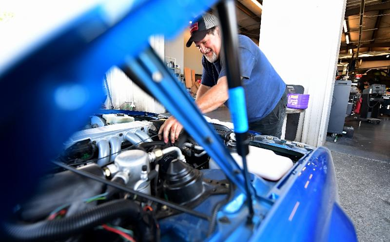 Keith Erwin, owner of Keith's Automotive, checks the engine of a vehicle at his shop's new location after having to move due to the high-speed railway line in Fresno, California (AFP Photo/Frederic J. BROWN)