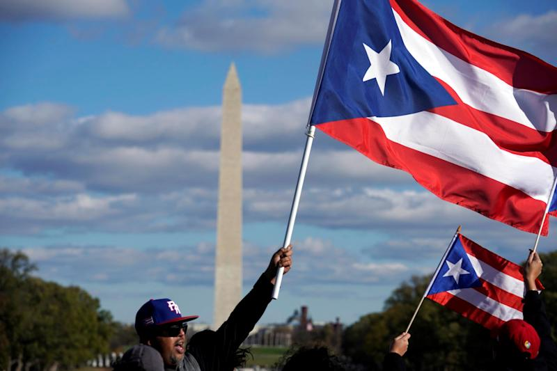 People wave Puerto Rican flags at the Unity March to highlight the ongoing humanitarian and natural disaster crisis in Puerto Rico, at the Lincoln Memorial in Washington, U.S., November 19, 2017: REUTERS