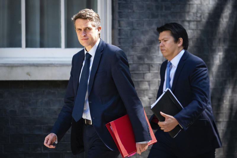 Britain's Secretary of State for Education Gavin Williamson, left, arrives in Downing Street after the introduction of measures to gradually bring the country out of lockdown, in London, Friday May 15, 2020. Education is one of the main sectors being considered with controversial factors about virus transmission and social distancing. The highly contagious COVID-19 coronavirus has impacted on nations around the globe, many imposing self isolation and exercising social distancing when people move from their homes. (Aaron Chown / PA via AP)
