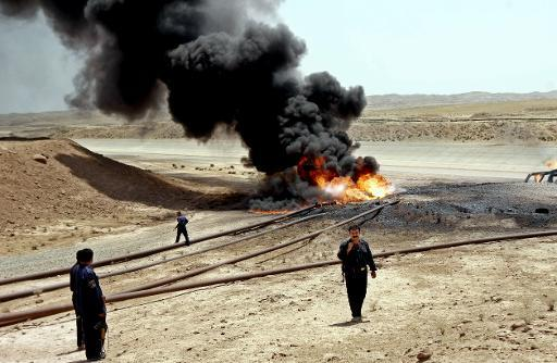 Members of the oil protection police secure the site of a burning oil pipeline near the northern city of Kirkuk, 03 July 2006