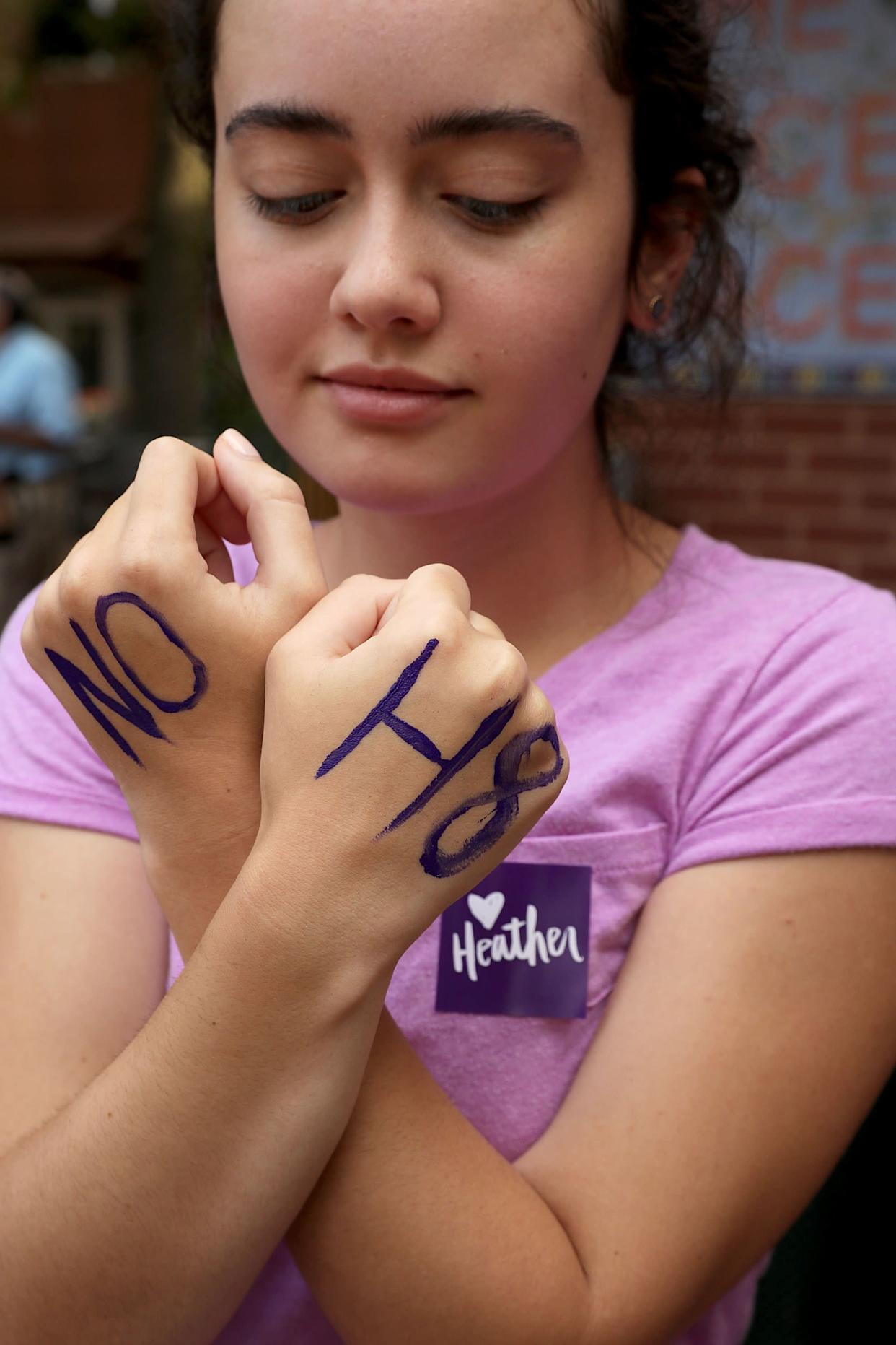 """Mia Jones shows off the """"NO H8"""" message written on her hands."""