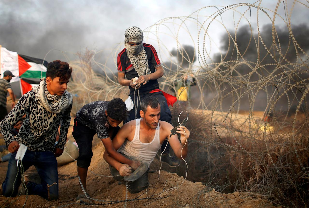 A disabled Palestinian is helped as he uses a sling to hurl stones at Israeli troops during a protest calling for lifting the Israeli blockade on Gaza and demanding the right to return to their homeland, at the Israel-Gaza border fence in Gaza October 19, 2018. Picture taken October 19, 2018. REUTERS/Mohammed Salem     TPX IMAGES OF THE DAY