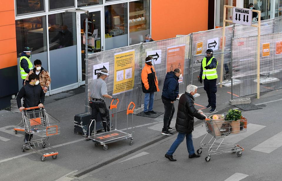 """Customers wearing face masks push shopping carts in front of a DIY store in Vienna, Austria, after it re-opened on April 14, 2020, following a """"shutdown"""" in a measure to limit the spread of the new coronavirus. (Photo by HELMUT FOHRINGER / APA / AFP) / Austria OUT (Photo by HELMUT FOHRINGER/APA/AFP via Getty Images)"""