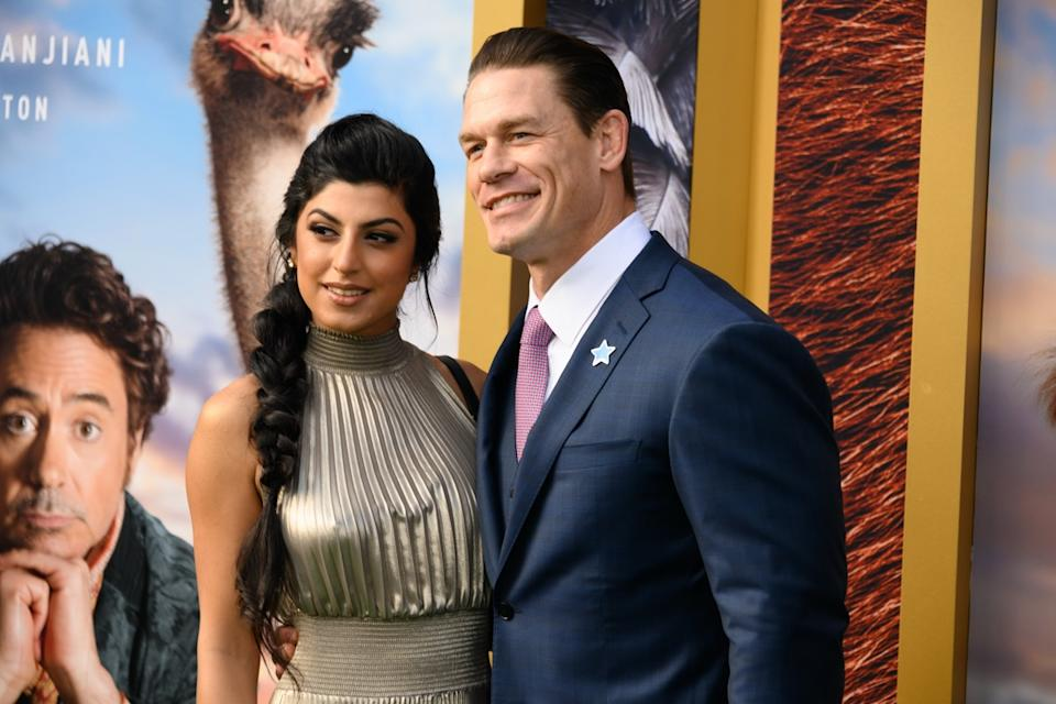 John Cena wears a blue suit and Shay Shariatzadeh wears a silver dress at the premiere of 'Dolittle' in 2020