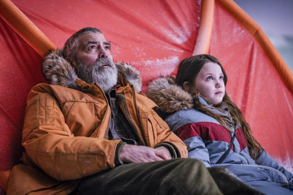 """This image released by Netflix shows Caoilinn Springall, right, and George Clooney in a scene from """"The Midnight Sky."""" (Philippe Antonello/Netflix via AP)"""