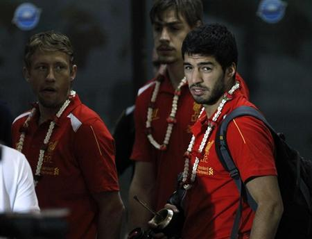 Liverpool's Luis Suarez (R), Lucas Leiva (L) and teammates arrive at Don Muang International Airport ahead of Sunday's soccer friendly against the Thai national team as part of Liverpool's Asia tour, in Bangkok July 25, 2013. REUTERS/Chaiwat Subprasom