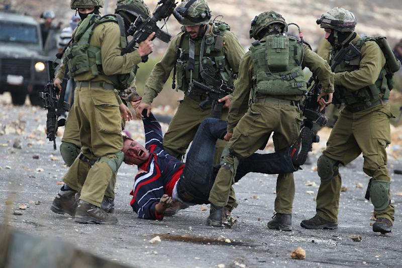 Israeli soldiers detain a wounded Palestinian stone thrower during clashes in Beit El, on the outskirts of the West Bank city of Ramallah, on October 7, 2015 (AFP Photo/Abbas Momani)