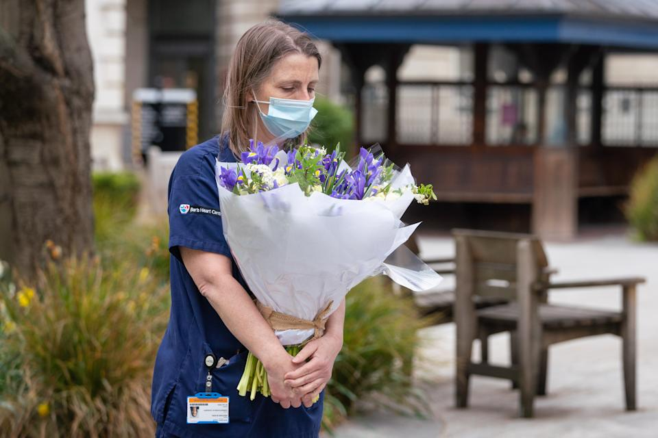 Staff at St Bartholomew's Hospital, London, receive flowers from Queen Elizabeth II on the anniversary of the first national lockdown to prevent the spread of coronavirus. Picture date: Tuesday March 23, 2021. (Photo by Dominic Lipinski/PA Images via Getty Images)