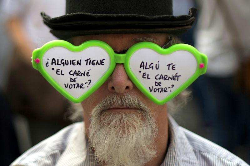 """A man wears sunglasses reading """"Who has the right to vote?"""" during a demonstration called by the """"Let's talk"""" association for dialogue over the Catalan crisis (AFP Photo/Jorge GUERRERO)"""