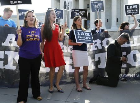 Anti-abortion rights protesters sing, chant and pray as they demonstrate outside the U.S. Supreme Court in Washington June 30, 2014. REUTERS/Jonathan Ernst