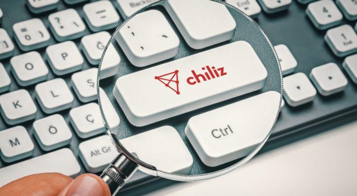 Hand holding a magnifying glass over a keyboard key that has the Chiliz altcoin logo on it