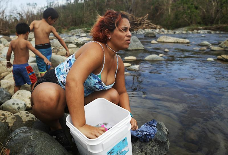 Maria Chiclano, who has no running water or power in her home, washes clothes with her sons in the Espiritu Santo river, more than two weeks after Hurricane Maria battered Puerto Rico.