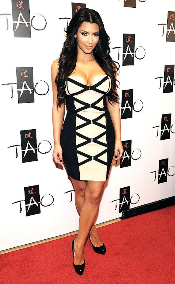 "Kim Kardashian showed off her sexy hour-glass figure in a hot cream and black criss-cross dress at the launch of her new fragrance at Tao nightclub in Las Vegas. Denise Truscello/<a href=""http://www.wireimage.com"" target=""new"">WireImage.com</a> - February 27, 2010"
