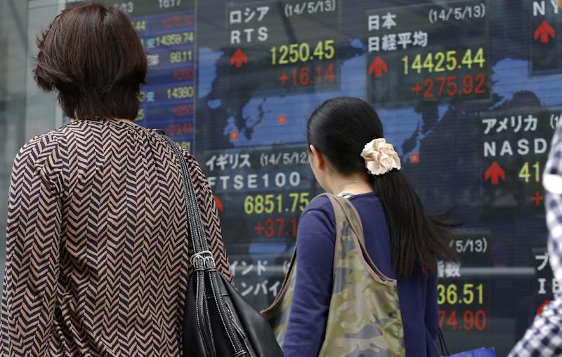 Women walk past an electronic stock indicator of a securities firm in Tokyo, Tuesday, May 13, 2014. Asian stock markets rose after Wall Street indexes hit record highs, with Japan's Nikkei 225 leading gains as the yen weakened. The Nikkei ended up 275.92 points at 14,425.44 on Tuesday. (AP Photo/Shizuo Kambayashi)