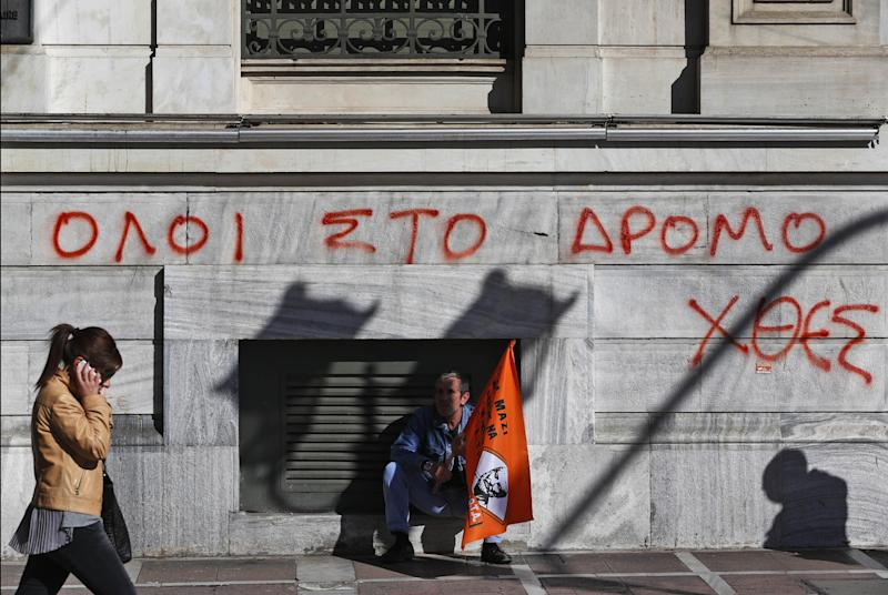 """A municipal worker participating in a anti-austerity rally sits in front of the National Bank of Greece building, underneath graffiti reading in Greek """"All to the streets yesterday"""", in central Athens, Friday, Nov. 9, 2012. Cash-strapped Greece will issue short term debt on Tuesday in the hope of raising enough money to repay a key bond days later. Greece is not expected to get its next batch of international rescue loans by Nov. 16, when it has to roll over 5 billion euros in three-month treasury bills. (AP Photo/Lefteris Pitarakis)"""