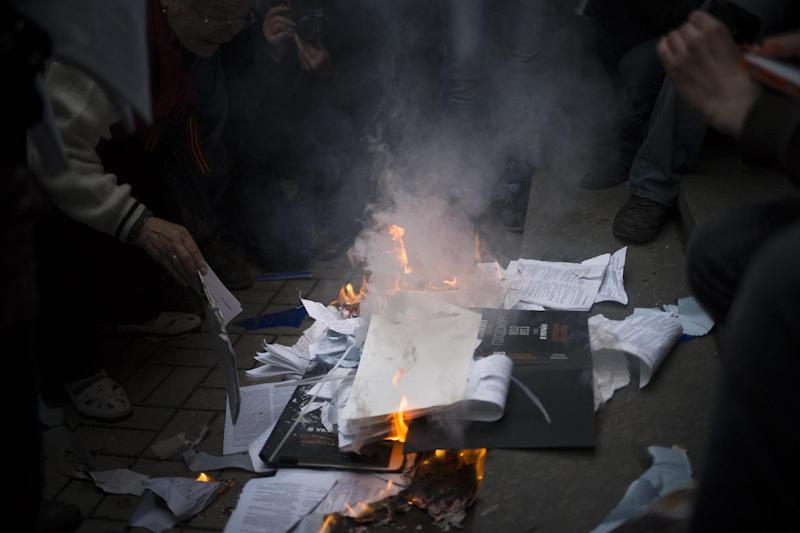 """Pro-Russian activists burn security documents seized when mobs stormed the Ukrainian regional office of the Security Service in Donetsk, eastern Ukraine, Saturday, May 3, 2014, which has been captured to honor the memory of fallen comrades during fighting with pro-Ukrainian activists in Odessa on Friday. In Donetsk, the largest city in the insurgent east, demonstrators who stormed the local office of the Ukrainian Security Service on Saturday evening shouted """"We will not forgive Odessa."""" No police were deployed to block the building takeover. (AP Photo/Alexander Zemlianichenko)"""
