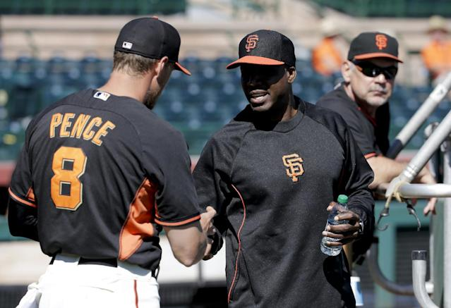 San Francisco Giants former player Barry Bonds, right, shakes hands with right fielder Hunter Pence during batting practice before a spring training baseball game between the Giants and the Chicago Cubs in Scottsdale, Ariz., Monday, March 10, 2014. Bonds starts a seven day coaching stint today. (AP Photo/Chris Carlson)