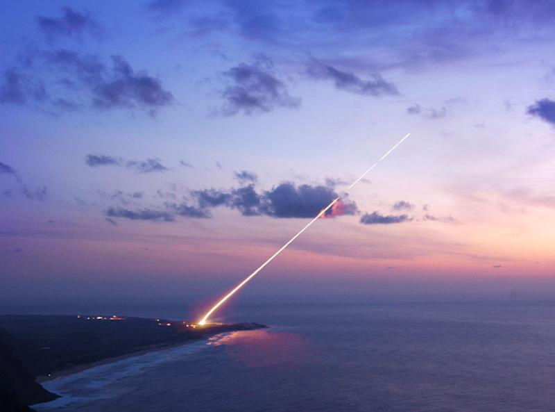 A missile fires off a pad and into the sunset.