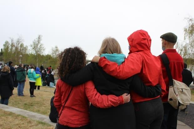 Three people hold each other while listening to speakers condemn racism and express support for the Islamic communities in Yellowknife at Thursday's vigil.
