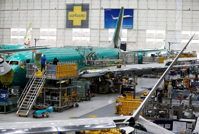 FILE PHOTO: People work near the door of a 737 Max aircraft at the Boeing factory in Renton