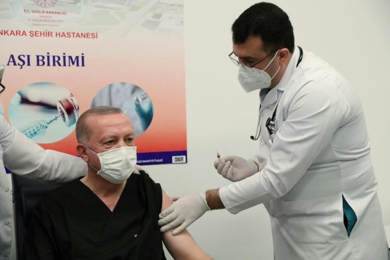 Seeking to set an example for Turks to get vaccinated, Turkish President Recep Tayyip Erdogan (C) receives the first dose of the CoronaVac Covid-19 vaccine at Ankara City Hospital.
