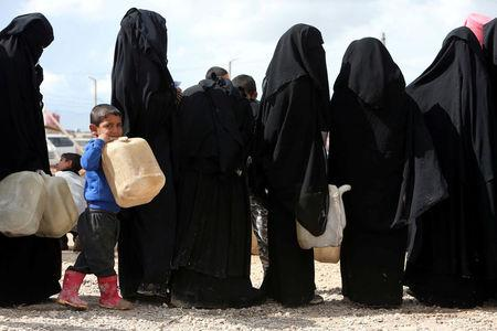 Women stand in line to get fuel at al-Hol displacement camp in Hasaka governorate