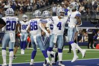 Dallas Cowboys' Tony Pollard (20), Dalton Schultz (86), Dak Prescott (4) and Cedrick Wilson (1) celebrate a touchdown catch made by Wilson in the second half of an NFL football game against the Carolina Panthers in Arlington, Texas, Sunday, Oct. 3, 2021. (AP Photo/Michael Ainsworth)