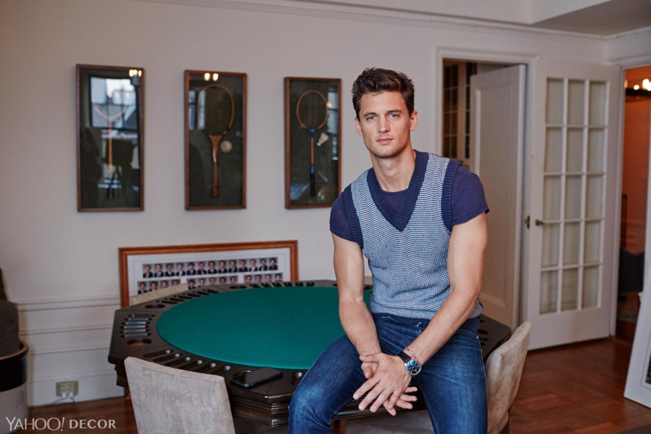 """<p>Neff took old squash, tennis, and badminton rackets from his grandparents' home and had them framed and mounted (he's a big racket sports fan). The photo lying against the wall is a composite of fraternity brothers, including Neff and his roommate. Here, Neff sits on a poker table that only occasionally gets used for game nights — """"I wish I could play more!"""" he says.</p>"""
