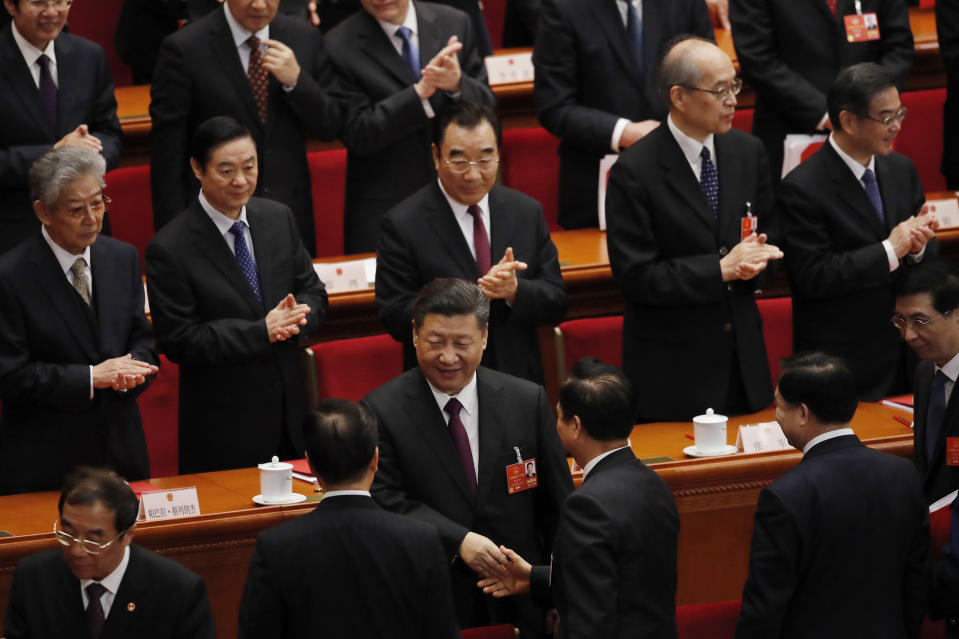 Chinese President Xi Jinping, center shakes hands with leaders on stage after the closing session of the annual National People's Congress (NPC) at the Great Hall of the People in Beijing, Tuesday, March 20, 2018. (AP Photo/Andy Wong)