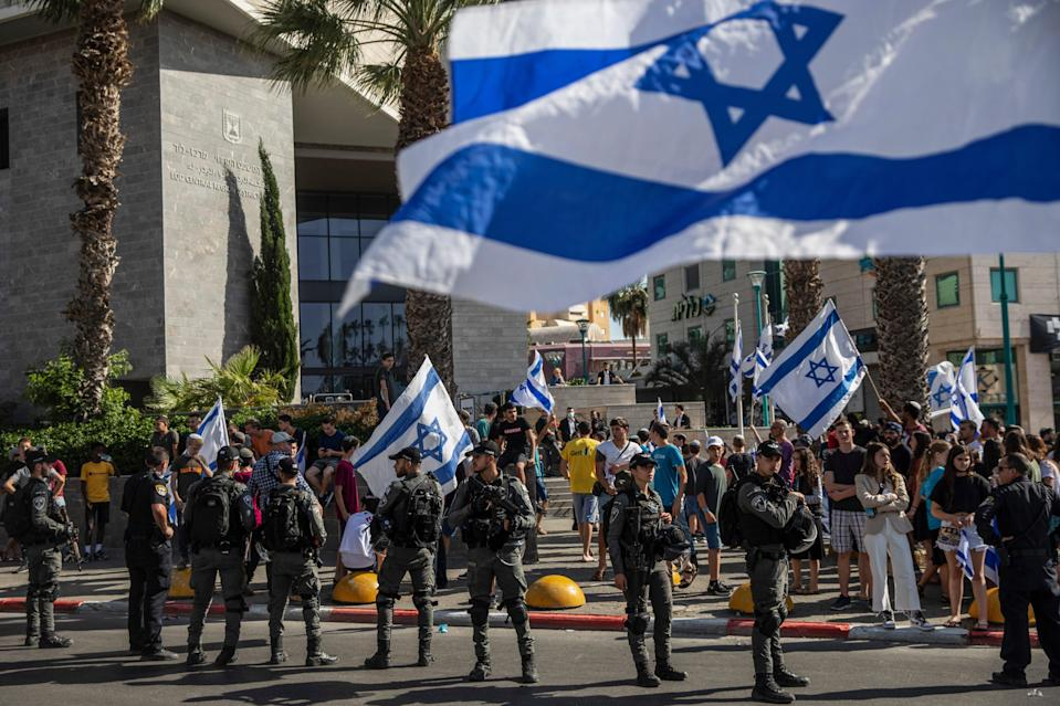 Israeli paramilitary border police stand guard outside the District Court in Lod as Jewish right-wing demonstrators demand the release of three Jews arrested over the shooting of Mussa HassunaAP
