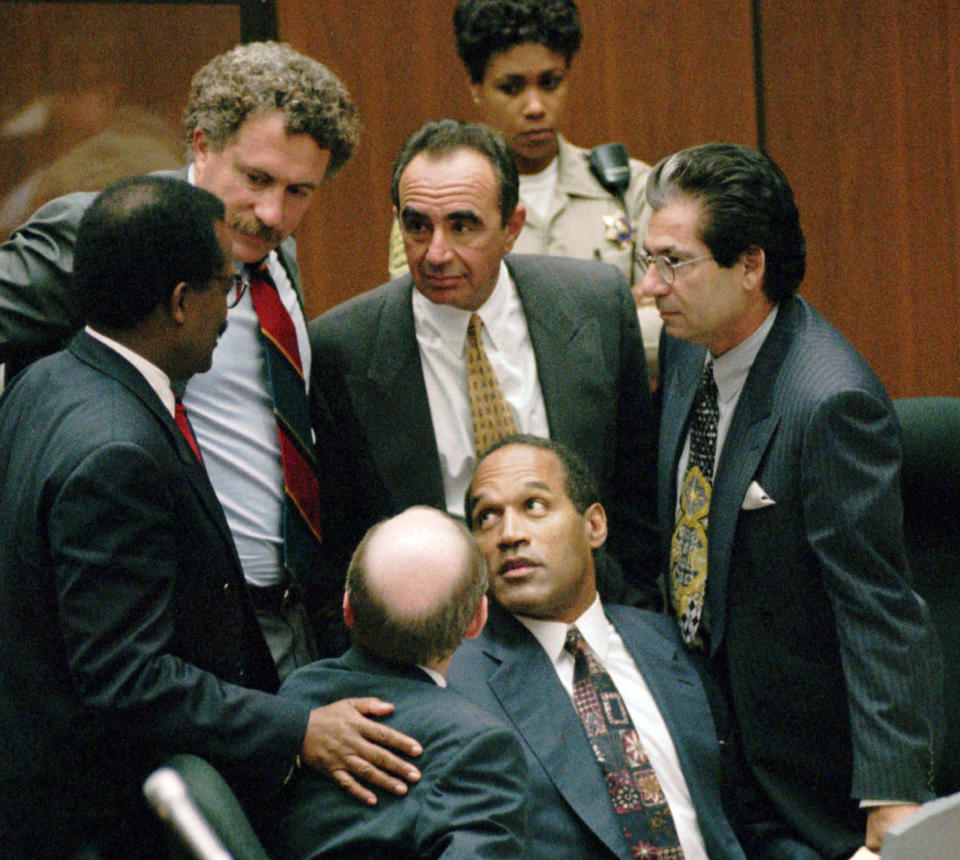 """FILE–In this Sept. 28, 1995 file photo, O.J. Simpson is surrounded by his """"Dream Team"""" defense attorneys from left, Johnnie L. Cochran Jr., Peter Neufeld, Robert Shapiro, Robert Kardashian, and Robert Blasier, seated at left, at the close of defense arguments in Los Angeles. (AP Photo/Sam Mircovich, Pool, File)"""