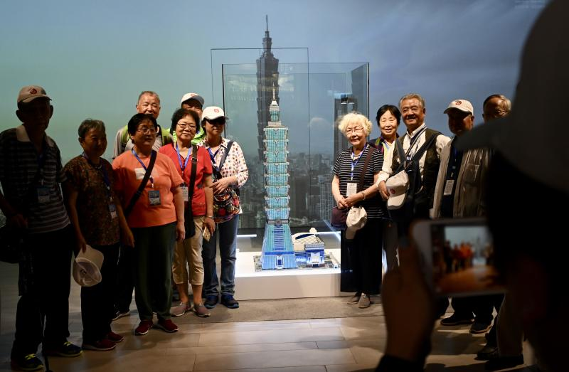 Tourists pose for photos next to a model of the Taipei 101, a 508-meter high commercial building, in Taipei on August 27, 2019. (Photo by Sam YEH / AFP) (Photo credit should read SAM YEH/AFP/Getty Images)