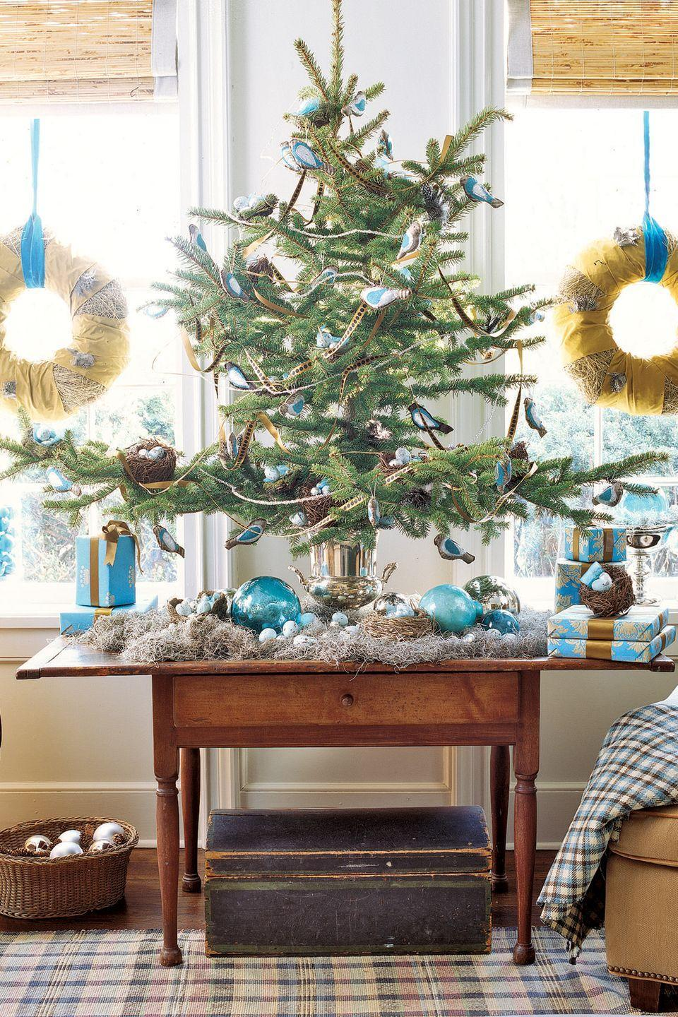 "<p>Vivid blues, bird ornaments, and faux nests give this tabletop tree a fun, outdoorsy feel.</p><p><a class=""link rapid-noclick-resp"" href=""https://www.amazon.com/Old-World-Christmas-Ornaments-Bunting/dp/B0026JQN0Y/?tag=syn-yahoo-20&ascsubtag=%5Bartid%7C10050.g.316%5Bsrc%7Cyahoo-us"" rel=""nofollow noopener"" target=""_blank"" data-ylk=""slk:SHOP BIRD ORNAMENTS"">SHOP BIRD ORNAMENTS</a></p>"
