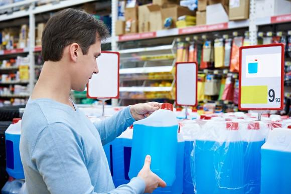 A customer shops for windshield wiper fluid in an auto parts store.