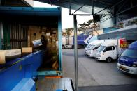 A worker loads parcels onto a conveyor belt from a delivery truck at a Hanjin Transportation distribution centre in Gwangju