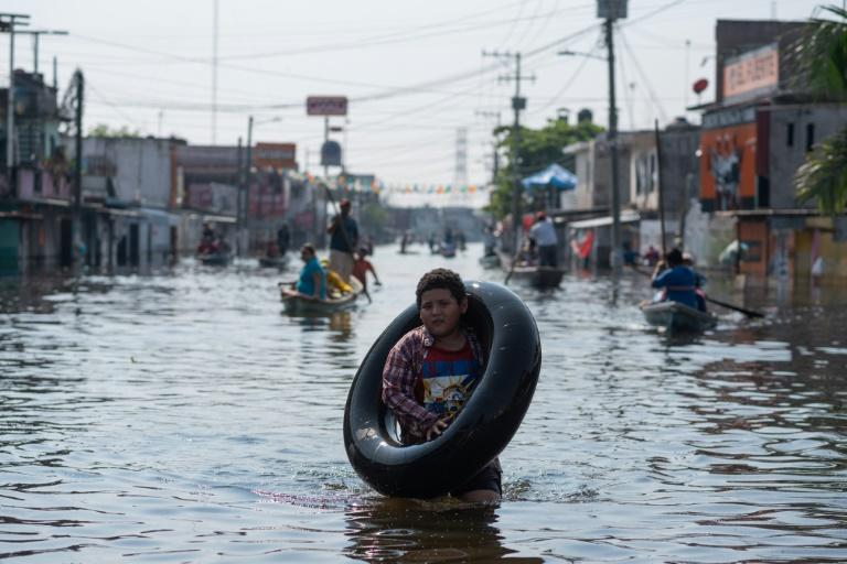 A boy wades through a flooded street in the Mexican city of Villahermosa. Thousands of people in Tabasco state have been forced to seek refuge in shelters due to flooding brought by Hurricane Eta and dischrge from an overflowing dam