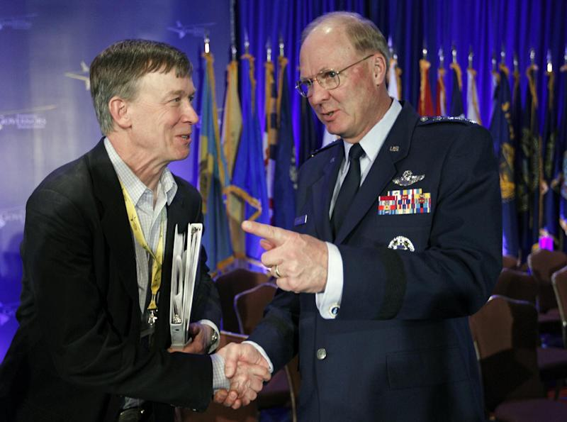 Colorado Gov. John Hickenlooper, left, shaske hands with Gen. Craig Richard McKinley Chief, National Guard Bureau at the Special Committee on Homeland Security and Public Safety panel during the National Governors Association winter meeting in Washington, Sunday, Feb. 26, 2012. ( AP Photo/Jose Luis Magana)