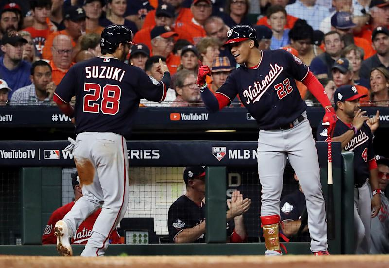 HOUSTON, TEXAS - OCTOBER 22: Kurt Suzuki #28 of the Washington Nationals is congratulated by his teammate Juan Soto #22 after scoring a run on a hit by Adam Eaton (not pictured) against the Houston Astros during the fifth inning in Game One of the 2019 World Series at Minute Maid Park on October 22, 2019 in Houston, Texas. (Photo by Elsa/Getty Images)