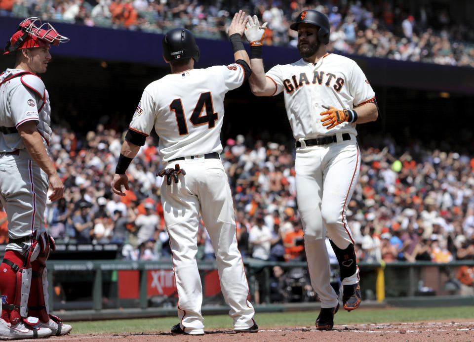San Francisco Giants' Evan Longoria, right, is congratulated by Scooter Gennett (14) after hitting a two-run home run off Philadelphia Phillies' Vince Velasquez (not shown) in the second inning of a baseball game in San Francisco, Saturday, Aug. 10, 2019. (AP Photo/Scot Tucker)