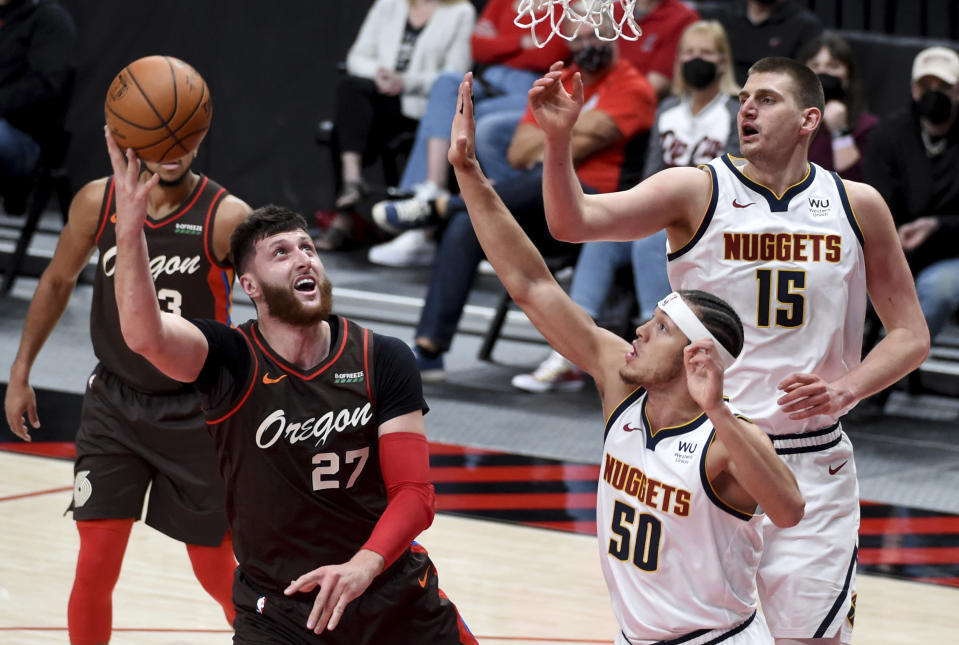 Portland Trail Blazers center Jusuf Nurkic, left, shoots the ball over Denver Nuggets forward Aaron Gordon, right, during the first half of an NBA basketball game in Portland, Ore., Sunday, May 16, 2021. (AP Photo/Steve Dykes)