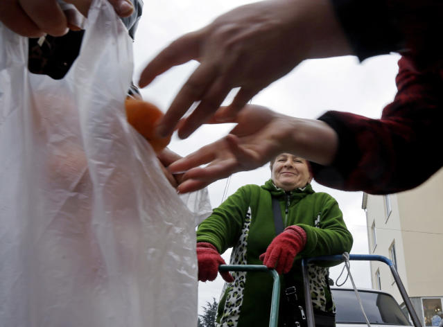 Mukhmunad Ashabokova watches as someone puts tangerines in a bag at the Abkhazian border Wednesday, Feb. 5, 2014, near Sochi, Russia. Most days in the tangerine season, she rolls her squat cart loaded down with the fruit across the bridge over Psou River from her garden about two miles inside Abkhazia. (AP Photo/Morry Gash)