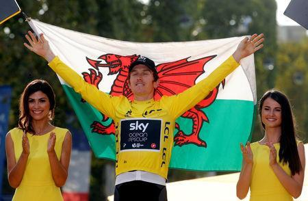 FILE PHOTO: Cycling - Tour de France - The 116-km Stage 21 from Houilles to Paris Champs-Elysees - July 29, 2018 - Team Sky rider Geraint Thomas of Britain celebrates his overall victory on the podium with a Welsh flag. REUTERS/Philippe Wojazer/File Photo