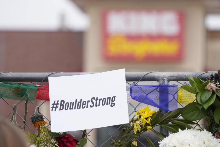 A sign tops the temporary fence line outside the parking lot of a King Soopers grocery store, the site of a mass shooting in which 10 people died, Friday, March 26, 2021, in Boulder, Colo. (AP Photo/David Zalubowski)