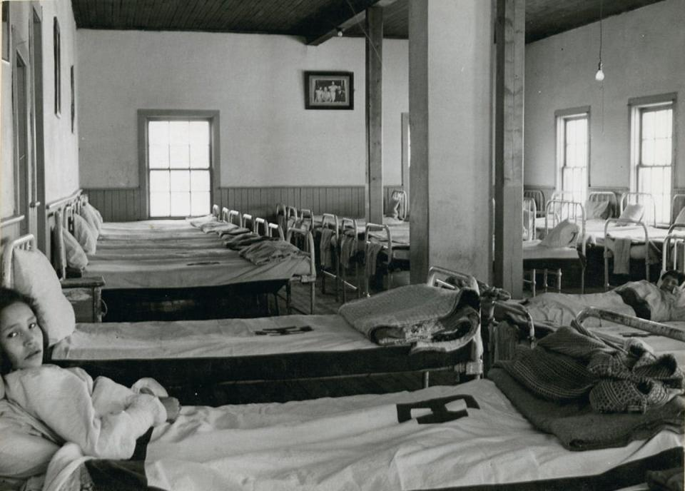 """<span class=""""caption"""">Two girls lay in bed in the dormitory at All Saints Indian Residential School in Lac La Ronge, Sask., in 1945.</span> <span class=""""attribution""""><span class=""""source"""">(Boorne & May. Library and Archives Canada, e010962312)</span>, <a class=""""link rapid-noclick-resp"""" href=""""http://creativecommons.org/licenses/by/4.0/"""" rel=""""nofollow noopener"""" target=""""_blank"""" data-ylk=""""slk:CC BY"""">CC BY</a></span>"""