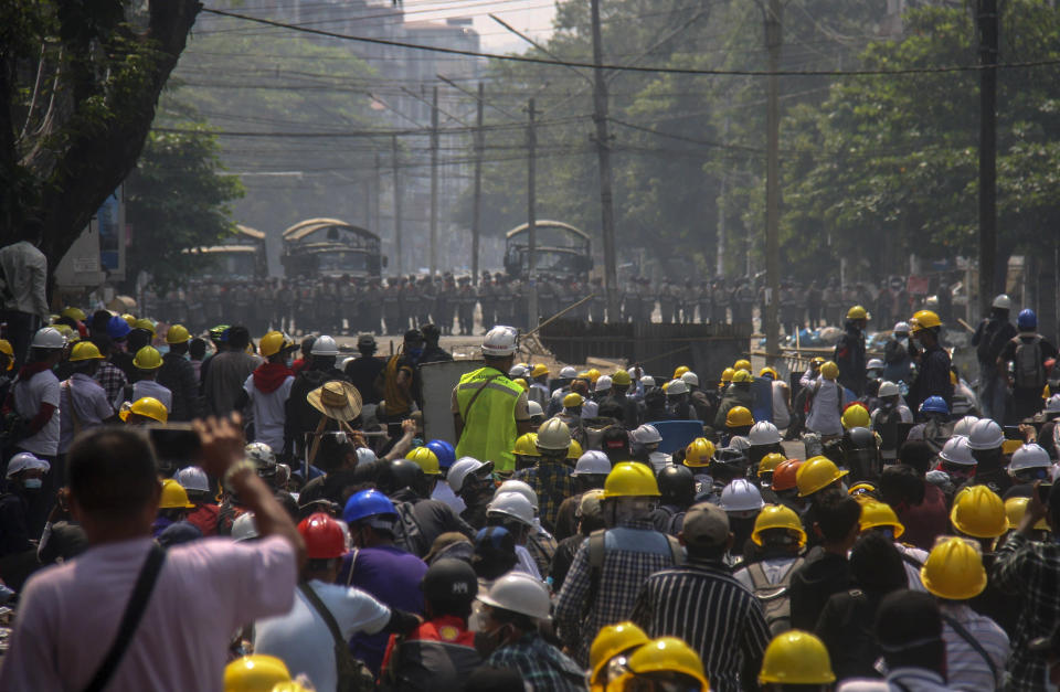 Anti-coup protesters, behind makeshift barricades stand off with Myanmar security forces in Yangon, Myanmar, Tuesday, March 2, 2021. Police in Myanmar repeatedly used tear gas and rubber bullets Tuesday against crowds protesting last month's coup, but the demonstrators regrouped after each volley and tried to defend themselves with barricades as standoffs between protesters and security forces intensified. (AP Photo)
