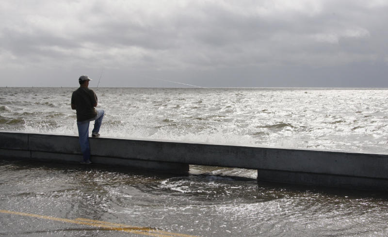 A fisherman takes advantage of the high tide and rising waves to try his hand at fishing from the seawall along Beach Boulevard in Waveland, Miss., as Tropical Storm Isaac's winds begin to hit the Mississippi Gulf Coast, Tuesday, Aug. 28, 2012. Forecasters at the National Hurricane Center warned that Isaac, especially if it strikes at high tide, could cause storm surges of up to 12 feet (3.6 meters) along the coasts of southeast Louisiana and Mississippi and up to 6 feet (1.8 meters) as far away as the Florida Panhandle. (AP Photo/Rogelio V. Solis)