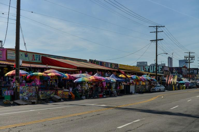 Shaded from the burning Californian sun by awnings and rainbow-colored umbrellas, customers advance slowly along a sidewalk crammed with stalls that burst into life every morning before being packed up and stashed away at night
