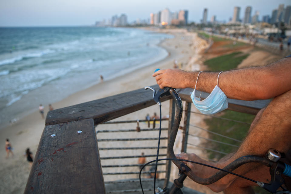 A man with a face mask on his arm watches the sunset on an almost deserted beach during a nationwide three-week lockdown to curb the spread of the coronavirus, in Tel Aviv, Israel, Monday, Sept 21, 2020. (AP Photo/Oded Balilty)