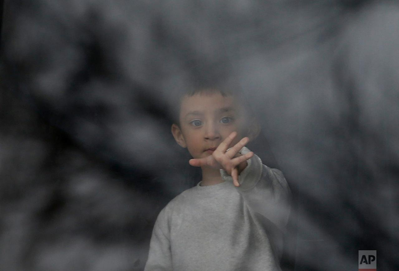 <p>A migrant boy watches through a window in the 'Krnjaca' refugee centre near Belgrade, Serbia. Several thousand migrants have been stuck in Serbia waiting for a chance to move on. (AP Photo/Darko Vojinovic) </p>